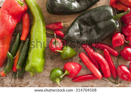 High Angle View of Assorted Red and Green Chili Peppers on a Rustic Wooden Table.