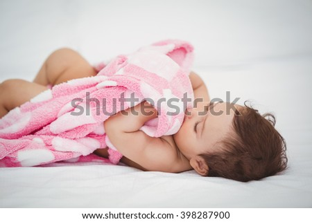 High angle view of baby holding blanket while lying on bed at home