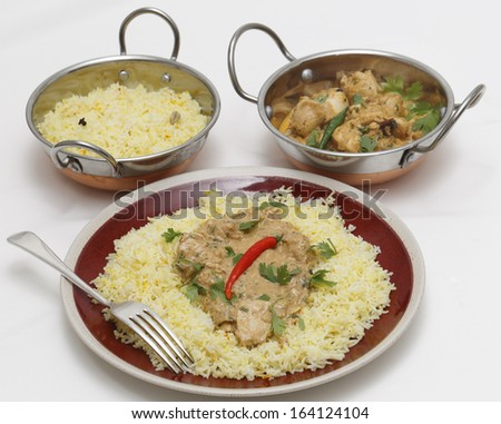 High angle view of balti chicken pasanda curry served on a bed of saffron rice, garnished with coriander leaves and a red chilli. This curry is made with yoghurt , cream and chopped coriander  - stock photo