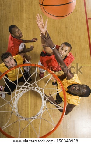 High angle view of basketball player attempting to slam dunk ball - stock photo