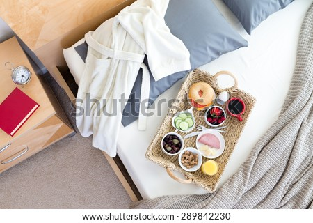 High Angle View of Bathrobe and Breakfast Tray on Unmade Bed Beside Night Table with Red Book in Hotel Room - stock photo