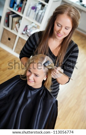 High angle view of beautician applying hair dye on female customer's hair - shallow DOF focus on hair stylist