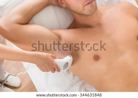 High Angle View Of Beautician Giving Laser Epilation Treatment On Man's Armpit - stock photo