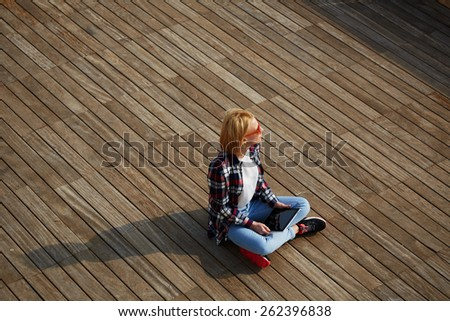 High angle view of beautiful teenager girl sitting with digital tablet looking into the distance, carefree bright future concept, young blond hair student sitting on wooden pier looking away - stock photo