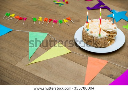 High angle view of birthday cake on decorated wooden table - stock photo