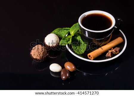 High Angle View of Black Coffee Served in Black Cup and Saucer with Fresh Mint Sprig, Cinnamon Stick and Star Anise, on Shiny Black Reflective Surface with Chocolate Covered Coffee Beans and Truffles - stock photo