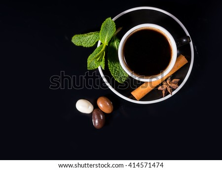 High Angle View of Black Coffee Served in Black Cup and Saucer with Fresh Mint Sprig, Cinnamon Stick and Star Anise, on Shiny Black Reflective Surface with Trio of Chocolate Covered Coffee Beans - stock photo