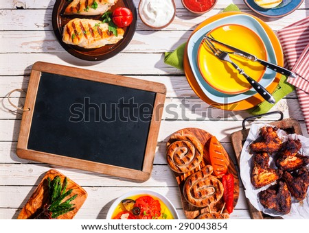 High Angle View of Blank Chalkboard on Picnic Table with Grilled Meal of Barbequed Meats and Vegetables - stock photo