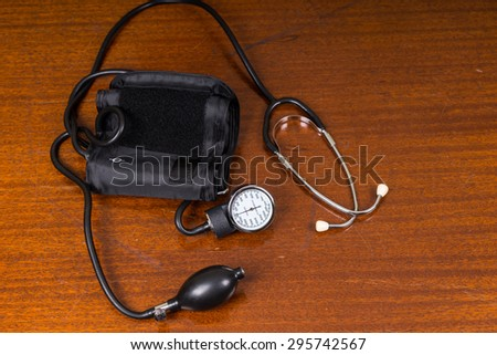 High Angle View of Blood Pressure Cuff and Stethoscope Medical Supplies on Wooden Table with Copy Space