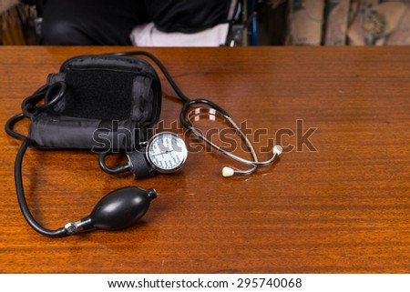 High Angle View of Blood Pressure Cuff and Stethoscope on Wooden Table with Copy Space - stock photo