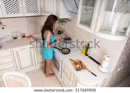High Angle View of Brunette Woman Cooking in Kitchen - Young Woman Preparing Meal on Stove Top in Kitchen at Home - stock photo