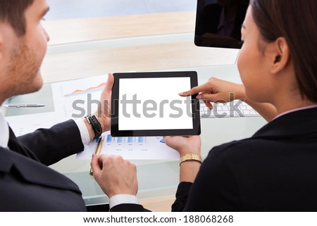 High angle view of business colleagues using digital tablet at desk in office - stock photo