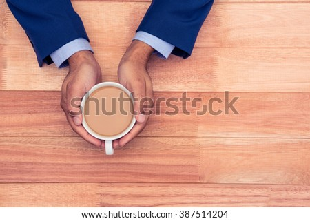 High angle view of business man holding coffee cup on wooden table - stock photo