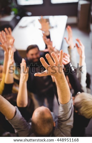 High angle view of business people cheering in creative office - stock photo