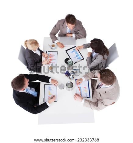 High angle view of business people discussing over financial graphs at conference table against white background