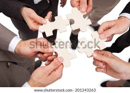High angle view of business people fixing jigsaw pieces over white background