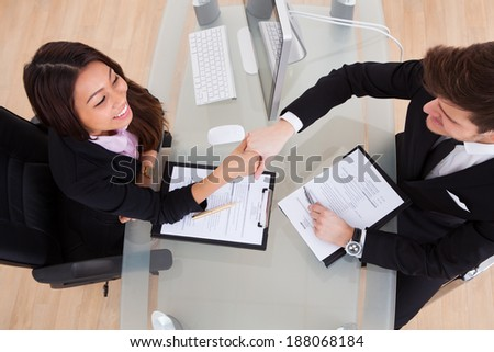 High angle view of business people shaking hands at desk in office - stock photo