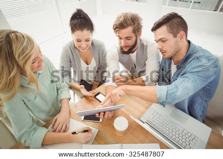 High angle view of business people using digital tablet while sitting at desk