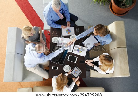 High angle view of business team sitting around the desk and shaking hands. Businesswomen and businessmen working with laptop and digital tablet while making business deal.  - stock photo