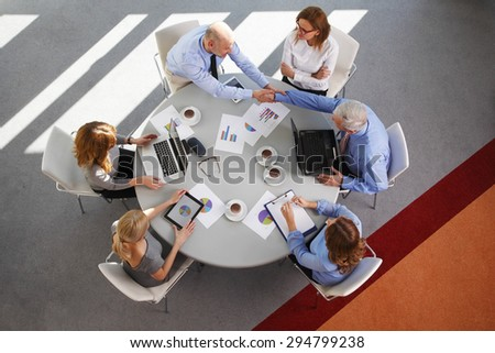 High angle view of business team sitting in a meeting while making deal and shaking hands. Group of business people using digital tablet and laptop while analyzing diagrams.