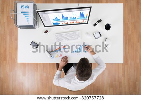 High Angle View Of Businessman Analyzing Statistical Graphs At Desk - stock photo