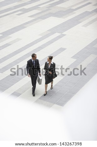 High angle view of businessman and businesswoman walking in outdoor plaza - stock photo