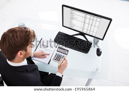 High angle view of businessman calculating expenses at desk in office - stock photo