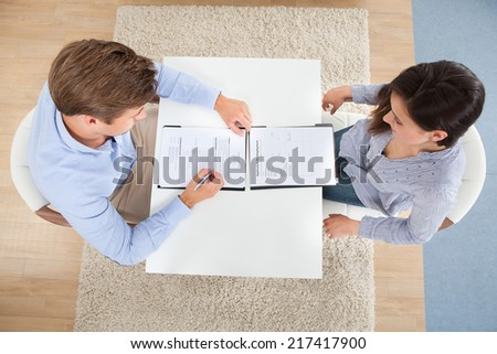 High angle view of businessman checking female candidate's resume in office - stock photo