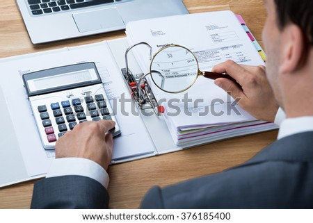 High angle view of businessman examining invoice with magnifying glass at office desk - stock photo