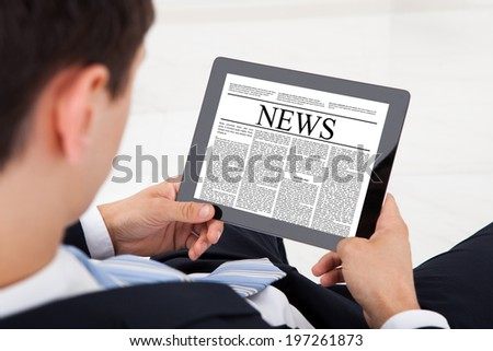 High angle view of businessman reading news on digital tablet in office