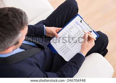 High Angle View Of Businessman Sitting On Couch Filling Customer Survey Form - stock photo