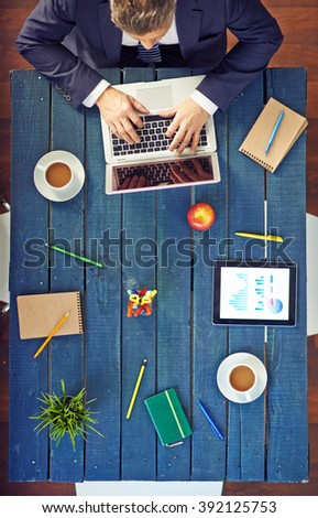 High angle view of businessman using laptop at desk in office