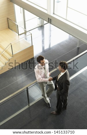 High angle view of businessmen shaking hands while standing by railing in office