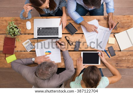 High angle view of businesspeople analyzing schemes and diagrams. Business team analyze growth of company. Businesspeople in meeting discussing future prospects and growth strategies in office.   - stock photo