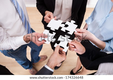 High Angle View Of Businesspeople Assembling Jigsaw Puzzle - stock photo