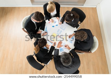 High Angle View Of Businesspeople Discussing Graph In Office - stock photo
