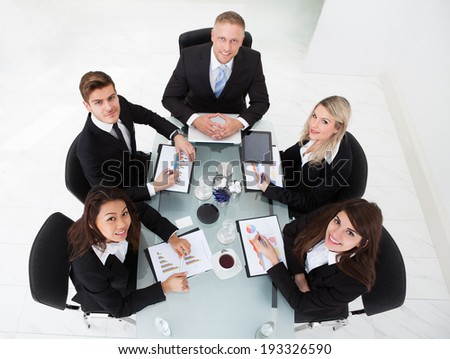 High angle view of businesspeople discussing in meeting at office desk - stock photo