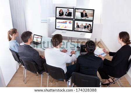 High Angle View Of Businesspeople In Video Conference At Business Meeting - stock photo