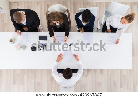 High Angle View Of Businesspeople Interviewing Young Male Applicant In Office