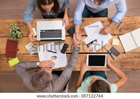High angle view of businesspeople shaking hands and closing a deal. Successful business teamwork working at the office. Business partners sitting at table and planning work.  - stock photo