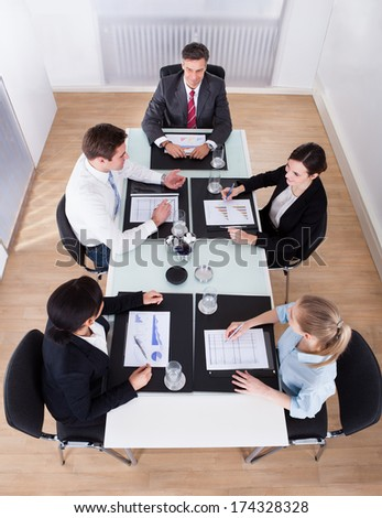 High Angle View Of Businesspeople Sitting In Conference At Office Desk - stock photo