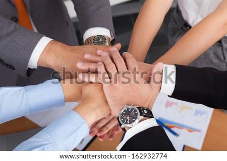 High Angle View Of Businesspeople Stacking Their Hands Together - stock photo