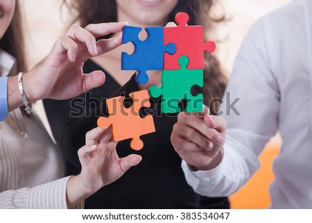 High Angle View Of Businesspeople Team Holding Colorful Puzzle Pieces In Hands
