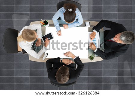 High Angle View Of Businesspeople Working Together At Desk - stock photo