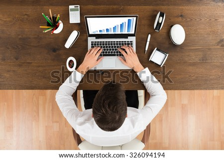 High Angle View Of Businessperson Analyzing Graph On Laptop At Desk - stock photo