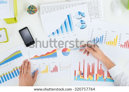 High Angle View Of Businessperson Analyzing Graphs At Desk