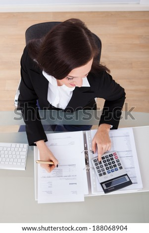 High angle view of businesswoman calculating tax at desk in office - stock photo