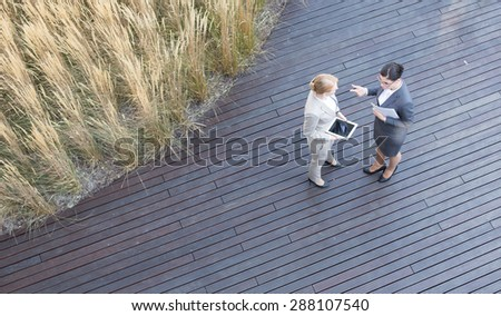 High angle view of businesswomen discussing while standing on floorboard - stock photo