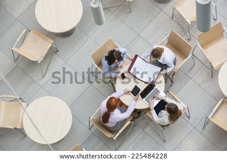 High angle view of businesswomen working in office canteen - stock photo