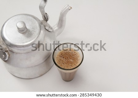 High angle view of chai in glass with an old fashioned kettle isolated over white background - stock photo